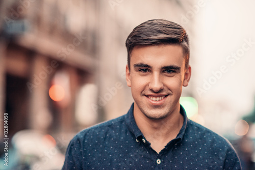 Photographie  Handsome young man smiling on a city street