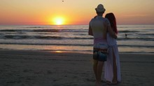 Couple Hugging And Kissing On The Shore Of A Sandy Beach At Sunset