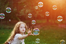 Crazy Little Girl Catching Soap Bubbles In The Summer Park.