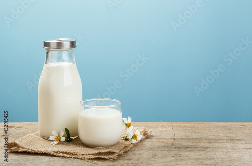 Canvas Print A bottle of rustic milk and glass of milk on a wooden table on a