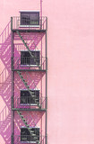 Fire escape metal on  light pink Vintage stone wall outside buil - 132920679