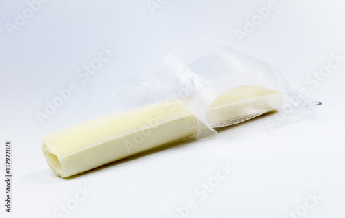 Fotografia, Obraz  Unwrapped mozzarella string cheese on a light colored background