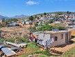 canvas print picture - Informal settlement - Enkanini with mountain and blue sky on the outskirts of Stellenbosch, Western Cape province, South Africa. Many shacks in Enkanini have solar panels for access to electricity.