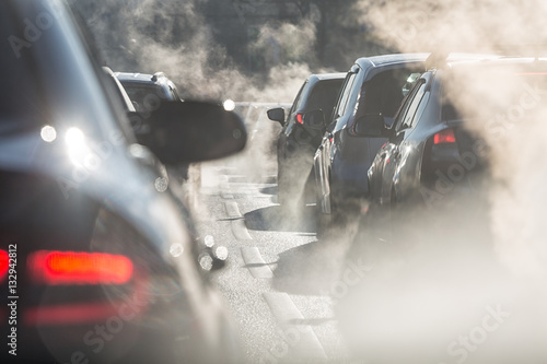 Fototapeta Blurred silhouettes of cars surrounded by steam from the exhaust