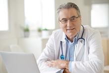 Portrait Of Senior Doctor Sitt...