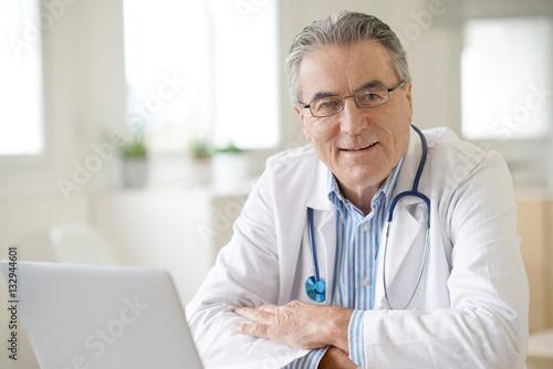 Stampa su Tela Portrait of senior doctor sitting in medical office