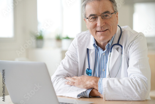 Fotografia  Portrait of senior doctor sitting in medical office