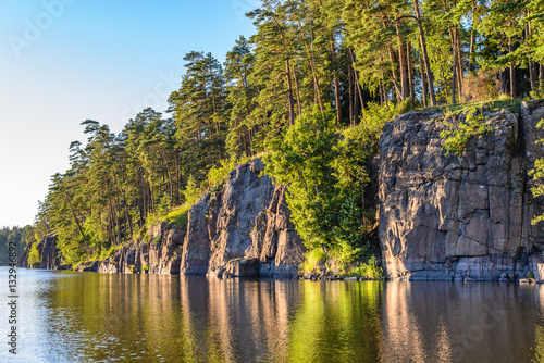 Fotografering  Steep rocky coast of the island of Valaam. Evening light. Square