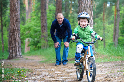 3a608dfd0a844 Little kid boy of 3 years and his father in autumn forest with a bicycle.  Dad teaching son. Man happy about success. Child helmet.