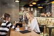 Two girlfriends in coffee shop looking at digital tablet