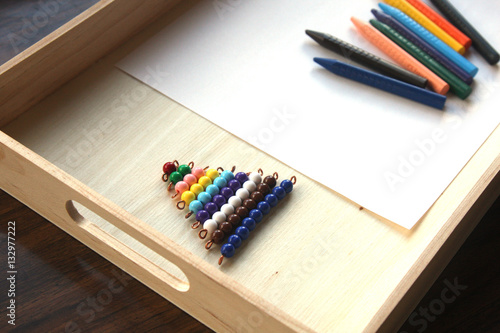 Valokuva  Colored beads on wooden tray with crayons and a piece of paper