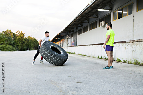Athlete exercising with tire outdoors