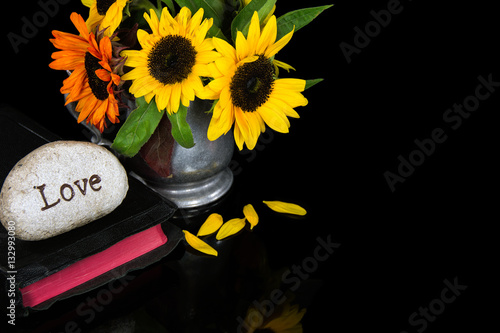 word love carved in stone on Holy Bible with sunflower