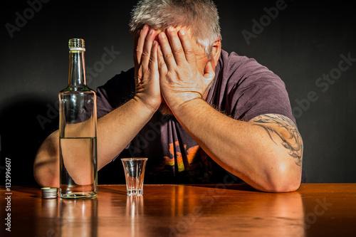 Valokuva  ein Mann sitzt mit einer Flasche Alkohol an einem Tisch