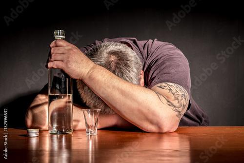 Fotografija  ein Mann sitzt mit einer Flasche Alkohol an einem Tisch
