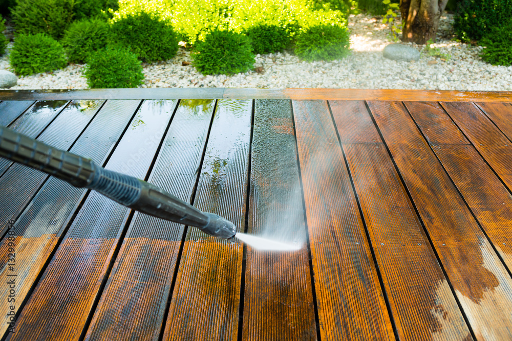 Fototapeta cleaning terrace with a power washer - high water pressure cleaner on wooden terrace surface