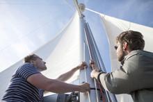 Two Men Hoisting Sail On Yacht