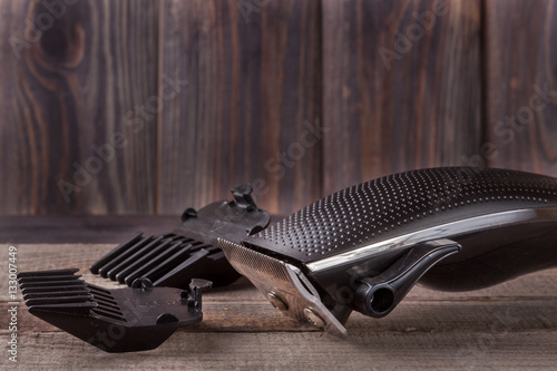 Photo  hair trimmer on an old wooden background closeup