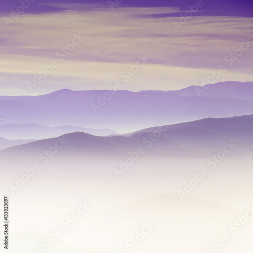 Spoed Foto op Canvas Lichtroze Mountain layer in morning sun ray and winter fog