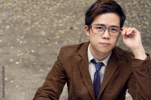 48bede2a05d Portrait Asian man with brown suit is holding his glasses and looking up.  copy space
