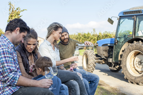 Group of friends drinking white wine on garden party in vineyard