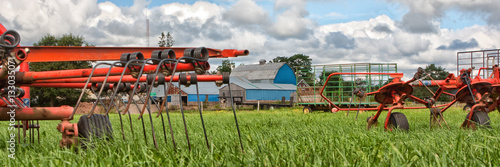 Banner of Red Farm Machinery in a Green Field Wallpaper Mural