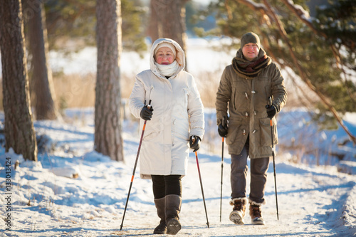 Poster Glisse hiver Winter sport in Finland - nordic walking. Senior woman and man hiking in cold forest. Active people outdoors. Scenic peaceful Finnish landscape.