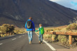 father with son walking on road, family travel