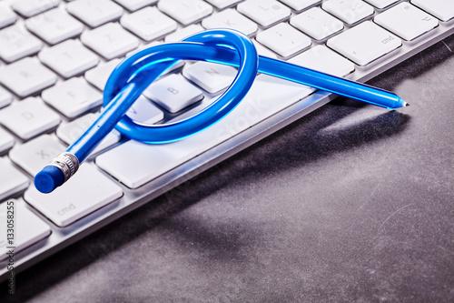 Valokuva  Knotted pencil on keyboard