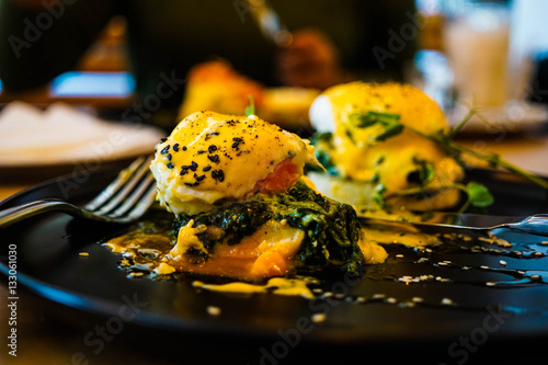 Canvas-taulu Eggs Florentine close up on a black plate with a fork also in sh