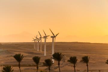 Duże turbiny wiatrowe na pustyni w tle zachodu słońca