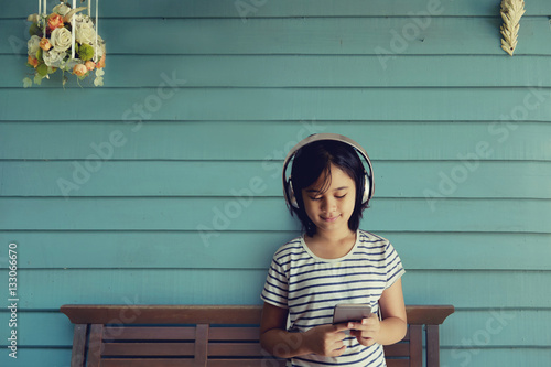 Happy smiling Asian Girl enjoys listens to music with
