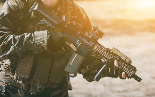 Fotografía  The soldier in the performance of tasks in camouflage and protective gloves holding a gun