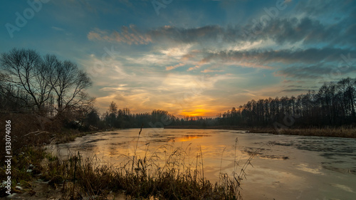 Tuinposter Groen blauw mysterious sunset over the freezing lake late autumn. landscape