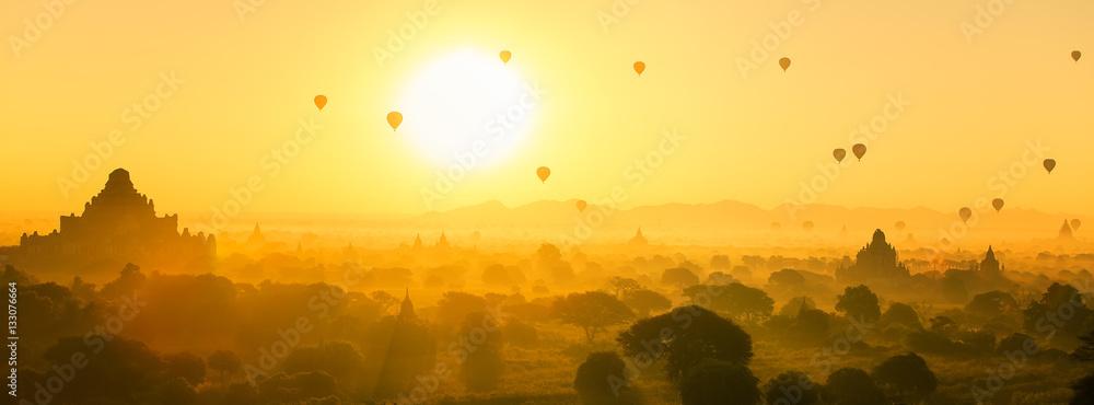Fototapeta Hot air balloon over plain and pagoda of Bagan in misty morning