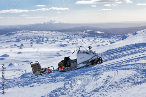 Snowmobile and sled on a mountain top. Winter mountain landscape