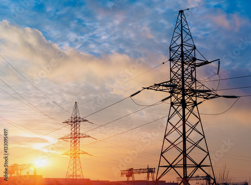 Fotografía  silhouette of power lines in the factory and sunset background.