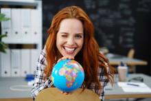 Frau Zeigt Einen Globus Und Zwinkert Mit Einem Auge