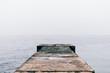 Leinwanddruck Bild - Old wet concrete pier on a cloudy day