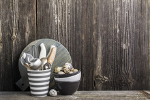 Kitchen Dining Utensils In Gray On A Wooden Table Against The Background Of   Wall With Quail And Chicken Eggs. In The Horizontal. Selective Focus