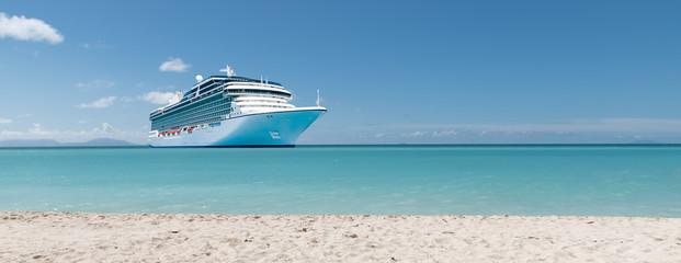 Summer vacation concept: Cruise ship in Caribbean Sea close to tropical beach.