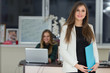 Beautiful smiling businesswoman holding file in office and woman working in the background.