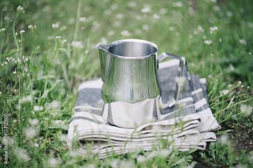 Obraz na plátně Frothing milk pitcher on the cloth napkin outdoors on the green grass background