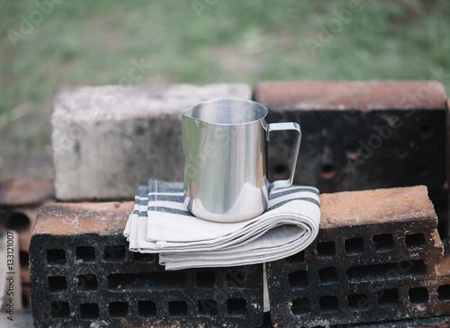 Obraz na plátně Frothing milk pitcher on the cloth napkin on the old red bricks