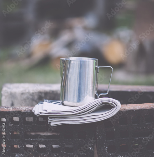 Fototapeta Frothing milk pitcher on the cloth napkin on the old red bricks