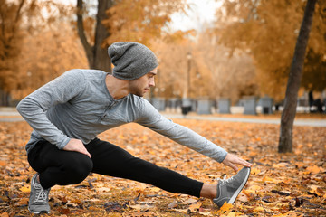 Handsome young man stretching in autumn park