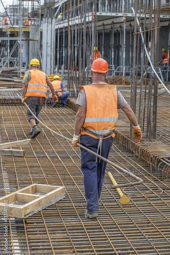 Valokuvatapetti Construction workers carrying heavy steel bar
