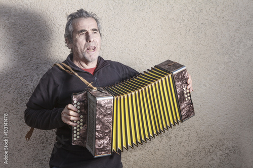 man playing accordion in the street Fototapet