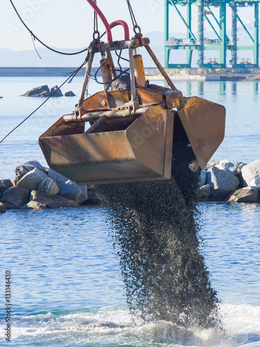 Photo  Dredge Clamshell Bucket unloading gravel in the water of a port next to the shor