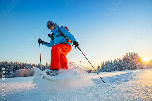 Tuinposter Wintersporten Snowshoe walker running in powder snow